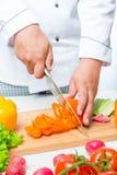 Ο αρχιμάγειρας κόβει τα πιπέρια στις λεπτές φέτες σε έναν ξύλινο πίνακα Στοκ εικόνα με δικαίωμα ελεύθερης χρήσης