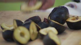 Ο αρχιμάγειρας κόβει τα ώριμα δαμάσκηνα με το μαχαίρι στον ξύλινο τέμνοντα πίνακα φιλμ μικρού μήκους