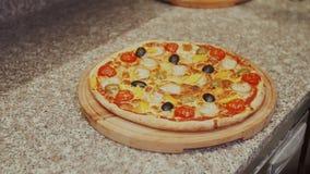 Ο αρχιμάγειρας κόβει τις πίτσες στο μετρητή στην κουζίνα απόθεμα βίντεο