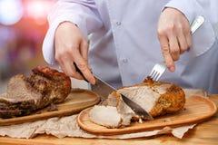 Ο αρχιμάγειρας κόβει το κρέας είναι μαγειρευμένος Στοκ Φωτογραφίες