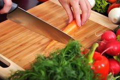 Ο αρχιμάγειρας κόβει το φρέσκο καρότο Στοκ Εικόνες