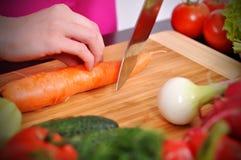 Ο αρχιμάγειρας κόβει το φρέσκο καρότο Στοκ Φωτογραφίες