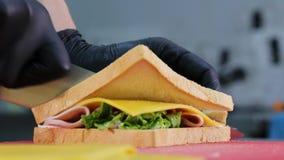 Ο αρχιμάγειρας μαγειρεύει το σάντουιτς με το ζαμπόν, το τυρί, μαρούλι και δύο φέτες του ψωμιού απόθεμα βίντεο