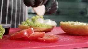 Ο αρχιμάγειρας μαγειρεύει το σάντουιτς με τη σάλτσα, τη μοτσαρέλα, το μαρούλι και τις ντομάτες απόθεμα βίντεο