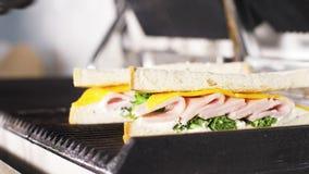 Ο αρχιμάγειρας μαγειρεύει το σάντουιτς σε μια ηλεκτρική σχάρα σε ένα εστιατόριο γρήγορου φαγητού απόθεμα βίντεο