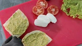 Ο αρχιμάγειρας μαγειρεύει το χορτοφάγο σάντουιτς με τη σάλτσα, τη μοτσαρέλα, το μαρούλι και τις ντομάτες φιλμ μικρού μήκους