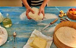 Ο αρχιμάγειρας νέων κοριτσιών ζυμώνει και κυλώντας τη ζύμη με την καρφίτσα Στοκ φωτογραφία με δικαίωμα ελεύθερης χρήσης