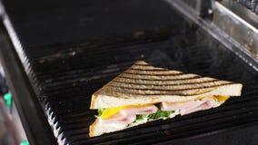 Ο αρχιμάγειρας παίρνει τα καυτά σάντουιτς από την ηλεκτρική σχάρα χρησιμοποιώντας ένα μαχαίρι απόθεμα βίντεο