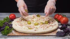 Ο αρχιμάγειρας παραδίδει τα γάντια σιλικόνης που παίρνουν ένα κομμάτι των τουρσιών στην εύγευστη φρέσκια πίτσα του Πλαίσιο Ιταλικ φιλμ μικρού μήκους