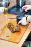 Ο αρχιμάγειρας που προετοιμάζει το κρέας και προσθέτει τα καρυκεύματα Στοκ Φωτογραφία