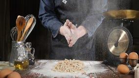 Ο αρχιμάγειρας που χτυπά τα χέρια με το αλεύρι κατασκευάζοντας τη ζύμη για την πίτσα, ζυμαρικά, ψήσιμο πασπαλίζει με ψίχουλα και  φιλμ μικρού μήκους