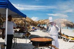 Ο αρχιμάγειρας προετοιμάζει ένα γιγαντιαίο paella θαλασσινών στην παραλία Varadero κάνοντας ηλιοθεραπεία πλησίον τους τουρίστες στοκ εικόνες