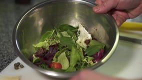 Ο αρχιμάγειρας προετοιμάζει μια εύγευστη σαλάτα με τα φρέσκα φύλλα λάχανων, τις ντομάτες κερασιών και το μαρούλι Η έννοια του μαγ φιλμ μικρού μήκους