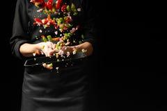 Ο αρχιμάγειρας προετοιμάζει τα λαχανικά στο τηγάνι Μαύρο υπόβαθρο για την αντιγραφή του κειμένου Επιχείρηση και διαφήμιση εστιατο στοκ εικόνα με δικαίωμα ελεύθερης χρήσης