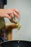 Ο αρχιμάγειρας προσθέτει τα συστατικά στα γεύματα Στοκ Φωτογραφίες
