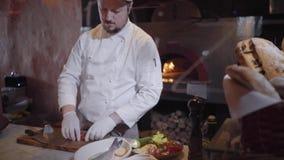 Ο αρχιμάγειρας στα άσπρα λαστιχένια γάντια έκοψε τις ντομάτες κερασιών λαχανικών, κρεμμύδι με το μεγάλο μαχαίρι και τις έβαλε στο φιλμ μικρού μήκους