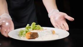 Ο αρχιμάγειρας στα γάντια που γυρίζει το πιάτο με η λωρίδα σολομών που εξυπηρετήθηκε με τα λαχανικά και το μαρούλι στο άσπρο πιάτ απόθεμα βίντεο