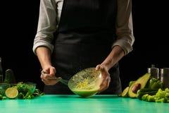 Ο αρχιμάγειρας στο μαύρο υπόβαθρο κτυπά το χυμό από τα λαχανικά για το μαγείρεμα των πράσινων καταφερτζήδων αποτοξίνωσης Υγιή, κα στοκ εικόνες