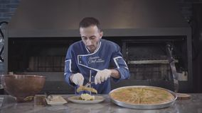Ο αρχιμάγειρας στο μπλε ομοιόμορφο και άσπρο λατέξ φορά γάντια να προετοιμαστεί για το ανατολικό γλυκό kunafa εξυπηρέτησης βάζοντ απόθεμα βίντεο