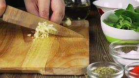 Ο αρχιμάγειρας τεμαχίζει το σκόρδο Μαχαίρι, τεμαχίζοντας πίνακας, σκόρδο Γρήγορη κοπή των λαχανικών Σκόρδο Σκόρδο για το τηγάνισμ φιλμ μικρού μήκους