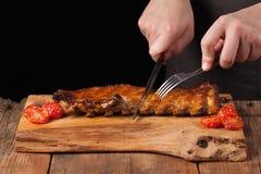 Ο αρχιμάγειρας το κόβει με ένα αιχμηρό μαχαίρι έτοιμο να φάει τα πλευρά χοιρινού κρέατος, σε έναν παλαιό ξύλινο πίνακα Ένα άτομο  Στοκ Φωτογραφίες
