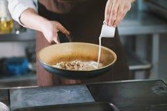 Ο αρχιμάγειρας χύνει τη σάλτσα στο κρέας στοκ φωτογραφίες