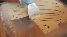 Ο αρχιμάγειρας χύνει το παγωτό στο τηγάνι παγώματος με τη σοκολάτα και το κυλά απόθεμα βίντεο