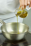 Ο αρχιμάγειρας χύνει το πετρέλαιο στο τηγάνι για τις πλήρεις συνταγές τροφίμων μαγειρέματος σειράς μαγειρέματος Στοκ Εικόνες