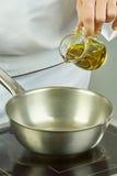 Ο αρχιμάγειρας χύνει το πετρέλαιο στο τηγάνι για τις πλήρεις συνταγές τροφίμων μαγειρέματος σειράς μαγειρέματος Στοκ Φωτογραφία
