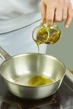 Ο αρχιμάγειρας χύνει το πετρέλαιο στο τηγάνι για τις πλήρεις συνταγές τροφίμων μαγειρέματος σειράς μαγειρέματος Στοκ Φωτογραφίες