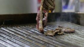 Ο αρχιμάγειρας ψήνει μια μπριζόλα στη σχάρα στη σχάρα απόθεμα βίντεο