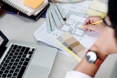 Ο αρχιτέκτονας ή ο εσωτερικός σχεδιαστής επιλέγει τους τόνους χρώματος για τις δημόσιες σχέσεις σπιτιών Στοκ Φωτογραφίες