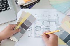 Ο αρχιτέκτονας ή ο εσωτερικός σχεδιαστής επιλέγει τους τόνους χρώματος για τις δημόσιες σχέσεις σπιτιών Στοκ Εικόνες