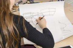 Ο αρχιτέκτονας γυναικών σύρει ένα σχέδιο, σχέδιο, γεωμετρικές μορφές από το μολύβι στο μεγάλο φύλλο του εγγράφου στο γραφείο γραφ Στοκ Εικόνες