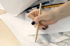 Ο αρχιτέκτονας γυναικών σύρει ένα σχέδιο, σχέδιο, γεωμετρικές μορφές από το μολύβι στο μεγάλο φύλλο του εγγράφου στο γραφείο γραφ Στοκ εικόνες με δικαίωμα ελεύθερης χρήσης