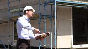 Ο αρχιτέκτονας επιθεωρεί την κατασκευή έξω από την ομιλία στο τηλέφωνο φιλμ μικρού μήκους