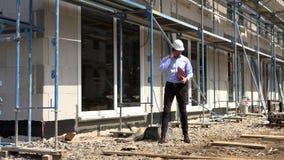 Ο αρχιτέκτονας επιθεωρεί την κατασκευή έξω από την ομιλία στο τηλέφωνο απόθεμα βίντεο