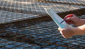 Ο αρχιτέκτονας κρατά τα έγγραφα με το πρόγραμμα και εξετάζει στοκ φωτογραφίες