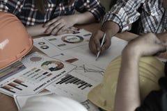 Ο αρχιτέκτονας με το επιχειρησιακό άτομο και ο μηχανικός προγραμματίζουν στο σχεδιάγραμμα Ο αρχιτέκτονας δείχνει στο σχεδιάγραμμα στοκ εικόνα