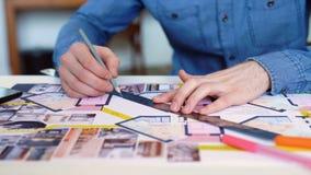 Ο αρχιτέκτονας που εργάζεται στο σχεδιάγραμμα με τα ειδικά εργαλεία και το μολύβι, κλείνει επάνω Αρσενικός αρχιτέκτονας στην εργα φιλμ μικρού μήκους
