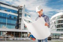 Ο αρχιτέκτονας στο κράνος εξετάζει τα σχεδιαγράμματα κοντά σε ένα εργοτάξιο Στοκ Εικόνες