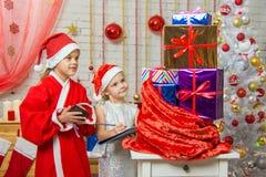 Ο αρωγός Άγιου Βασίλη και αντιπαραβάλλει έναν κατάλογο δώρων Στοκ Εικόνες