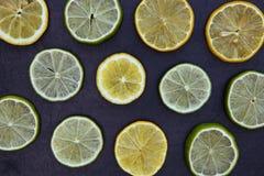 Ο ασβέστης λεμονιών τεμαχίζει τα τρόφιμα στο σκοτεινό υπόβαθρο Στοκ Εικόνες