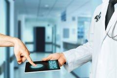Ο ασθενής αφήνει ένα δακτυλικό αποτύπωμα στην ταμπλέτα γιατρών ` s στην επιβεβαίωση της συγκατάθεσης στη θεραπεία Σύγχρονη τεχνολ Στοκ Φωτογραφία