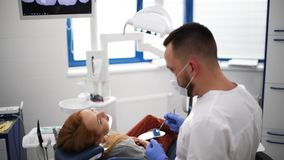 Ο ασθενής στο γραφείο οδοντιάτρων κάνει την προφορική υγιεινή την οδοντική θεραπεία κατά τη διάρκεια της χειρουργικής επέμβασης φιλμ μικρού μήκους