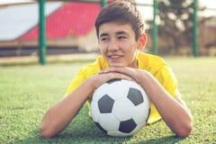 Ο ασιατικός έφηβος αγοριών με μια σφαίρα ποδοσφαίρου βρίσκεται στη χλόη αθλητισμός Στοκ Εικόνα