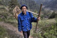 Ο ασιατικός αγρότης πηγαίνει να εργαστεί στους τομείς με το δίκρανο σκαπανών Στοκ Εικόνα