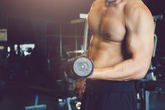 Ο ασιατικός αθλητικός τύπος αυξάνει τον αλτήρα με το μυϊκό κτήριο στη γυμναστική Στοκ Φωτογραφία