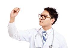 Ο ασιατικός αρσενικός γιατρός με το σοβαρό πρόσωπο εξετάζει το θερμόμετρο Στοκ Εικόνες
