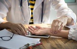 Ο ασιατικός γιατρός κινηματογραφήσεων σε πρώτο πλάνο ελέγχει το σφυγμό υπομονής ` s από τα δάχτυλα στοκ φωτογραφία με δικαίωμα ελεύθερης χρήσης